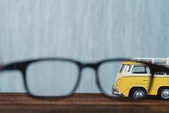Смотрящ до eyeglasses для минифургона игрушки на деревянном столе стоковое фото