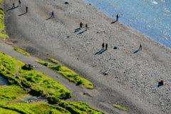Смотрящ правый спуск на людях рекой Skogar, около Skogafoss Стоковые Фото