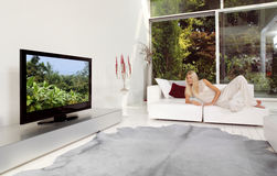 Смотрящ ТВ дома Стоковая Фотография