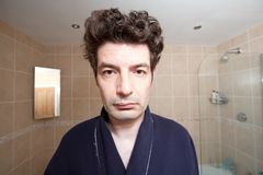 смотрящ утомлянное зеркало человека Стоковая Фотография