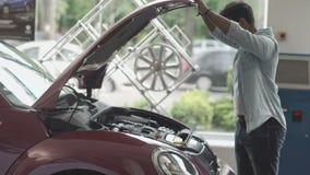 Смуглый парень проверяет мотор современного автомобиля в автосалоне сток-видео