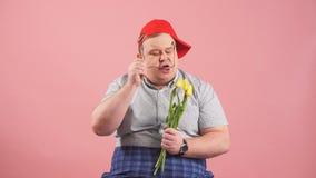 Смущаясь девушка пухлого человека ждать с цветками на розовой предпосылке акции видеоматериалы