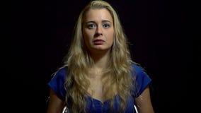 Смущение красивой сексуальной белокурой девушки в голубом платье в студии с черной предпосылкой сток-видео