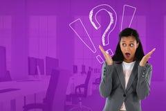 Смущенная или удивленная женщина смотря налево в офисе с возгласом и вопросительными знаками Стоковое фото RF