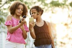 Смущенные девушки проверяя информацию на смартфонах стоковая фотография rf