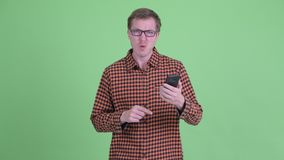 Смущенный молодой человек хипстера используя телефон и смотреть сотрясенный сток-видео