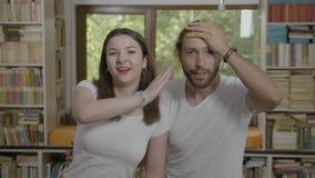 Смущенный тысячелетний человек шлепая его лоб делая facepalm затем его пары подруги счастливые смешные имея потеху - сток-видео