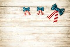 3 смычка американских флага на деревенской деревянной предпосылке доски с комнатой или космосе для экземпляра, текста Горизонталь Стоковое Изображение RF