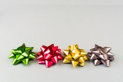 4 смычка цвета праздничных над серой предпосылкой Стоковое фото RF