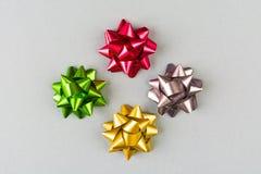 4 смычка цвета праздничных над серой предпосылкой Стоковая Фотография