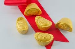 Смычок ленты золотого ингота красный на белой предпосылке Стоковая Фотография