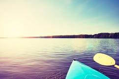 Смычок каяка на неподвижном озере на заходе солнца Стоковые Фото