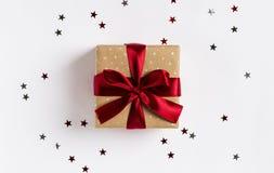 Смычок коробки праздничного подарка рождества красный на украшенной праздничной таблице с искрой играет главные роли Стоковое Фото