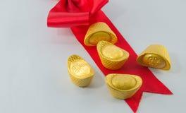 Смычок ленты золотого ингота красный на белой предпосылке Стоковое Изображение