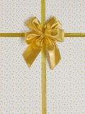 Смычок подарка с золотой лентой сатинировки Стоковое фото RF