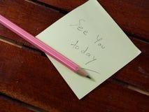 См. вас сегодня, пишущ на желтой бумаге стикера и розовом карандаше на деревянной предпосылке стоковое фото rf