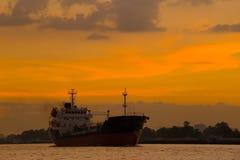 Снабжение и транспорт международного грузового корабля контейнера в океане на заходе солнца, и силуэт большой шлюпки Стоковая Фотография RF
