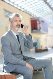 Снаружи бизнесмена сидя говоря на телефоне Стоковые Фото