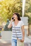 Снаружи более старой женщины идя говоря на мобильном телефоне в городе Стоковые Фото