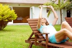 Снаружи женщины расслабляющее с книгой Стоковое Фото