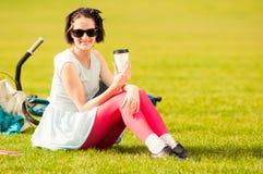 Снаружи жизнерадостной красивой женщины расслабляющее с чашкой кофе стоковые фотографии rf