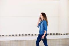 Снаружи жизнерадостной молодой женщины идя говоря на мобильном телефоне Стоковые Изображения