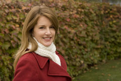 Снаружи зрелой женщины стоящее нося красное пальто Стоковые Изображения RF