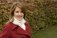 Снаружи зрелой женщины стоящее нося красное пальто Стоковые Фото