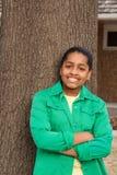 Снаружи и усмехаться молодого Афро-американского девочка-подростка стоящее Стоковые Изображения