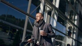 Снаружи красивого привлекательного кавказского бизнесмена идя, держащ планшет и выпивающ кофе около большого офиса видеоматериал