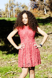 Снаружи красного платья молодой женщины стоящее на траве Стоковая Фотография