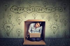 снаружи принципиальной схемы коробки думает Женщина сидя внутри коробки используя работу на портативном компьютере Стоковое Изображение RF