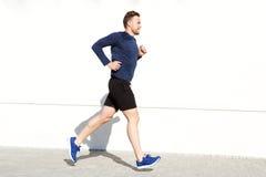 Снаружи счастливого человека идущее против белой стены Стоковое Фото