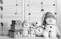Снеговики, плюшевые медвежоата и коробки настоящего момента приближают к будильнику стоковое фото rf