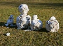 Снеговики сделанные с снежными комьями и украшенные хворостинами на солнечном da Стоковое фото RF