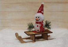 Снеговик в красной крышке с деревянными санями Стоковые Изображения