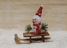 Снеговик в красной крышке с деревянными санями Стоковое Изображение RF