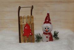 Снеговик в красной крышке с деревянными санями Стоковая Фотография RF