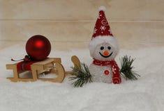 Снеговик в красной крышке с деревянными санями Стоковое Изображение