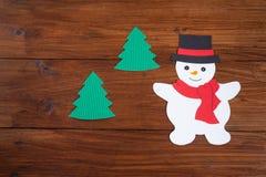 Снеговик и ели на древесине Стоковые Изображения