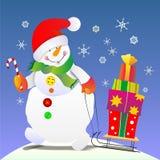 Снеговик носит подарки на рождество на розвальнях Стоковое фото RF