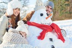 Снеговик семьи играя и строя Стоковая Фотография RF