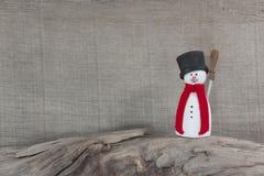 Снеговик стоя на хоботе для рождества - деревянной предпосылки Стоковое фото RF