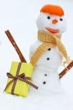 Снеговик с шарфом и tangerine слезают, подарок для рождества, предпосылки белого снега Стоковое Изображение RF