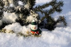 Снеговик фарфора в снеге под деревом Стоковая Фотография