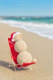 Снеговик Sandy в шляпе santa загорая в салоне пляжа Стоковое Изображение