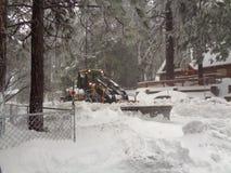 Снегоочиститель освобождая жилую улицу в бежать веснах, горах CA Сан Бернардино стоковое изображение