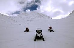 Снегоходы и люди в горах стоковые изображения rf