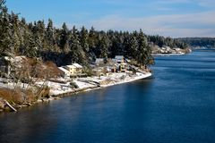 Снег-запыленный городок между древесинами и водой стоковые фото