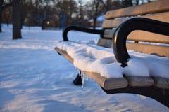Снег зимы на скамейке в парке стоковые изображения